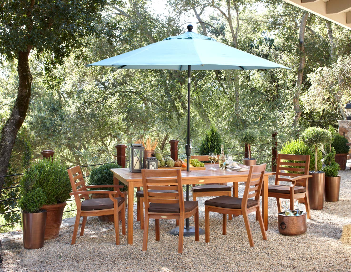 Teak wood dinning furniture with green umbrella in pea gravel