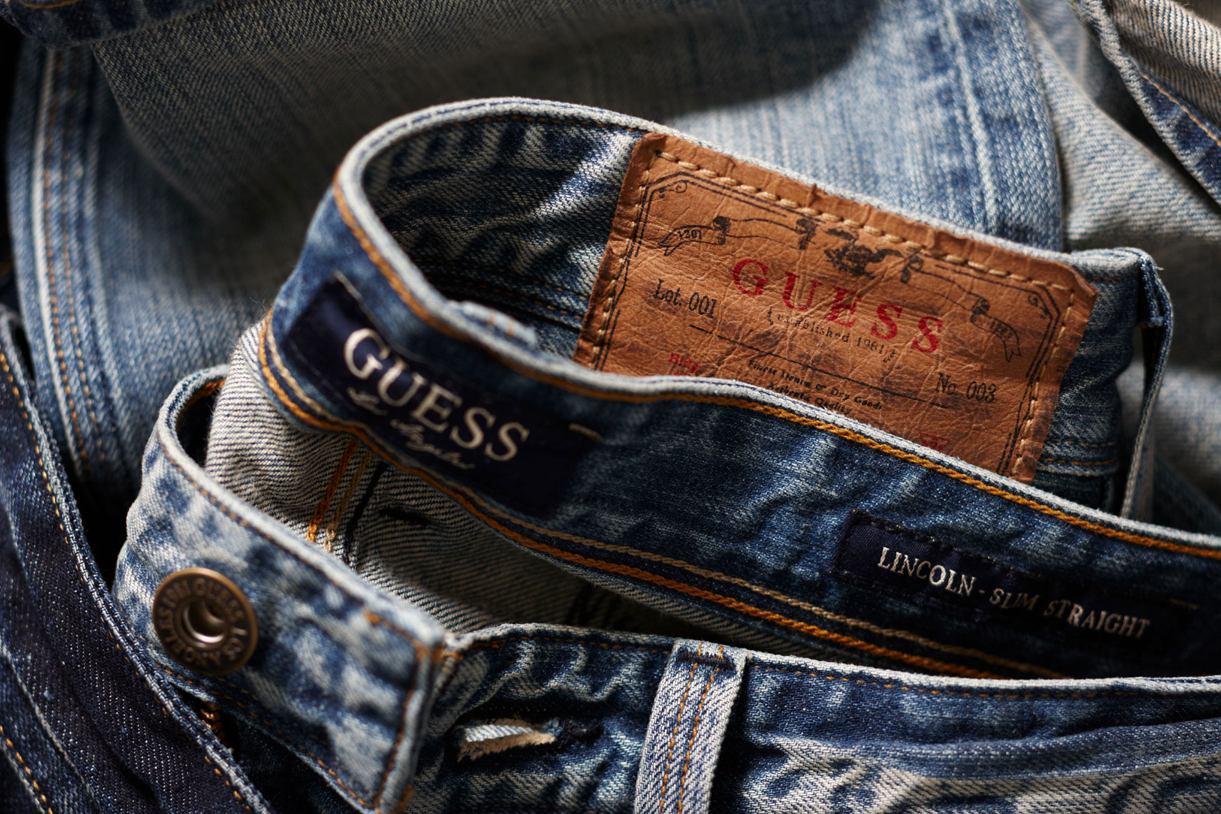 detail of waistbands of light and dark denim jeans