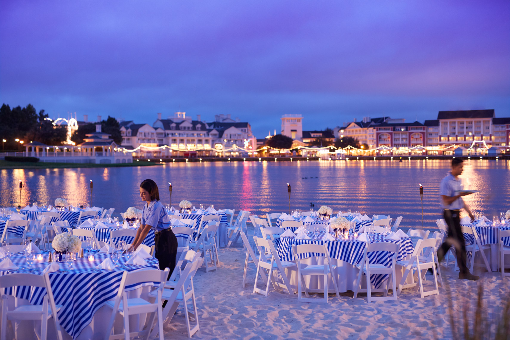 Servers preparing tables for outdoor dining on the beach at sunset with reflections on water