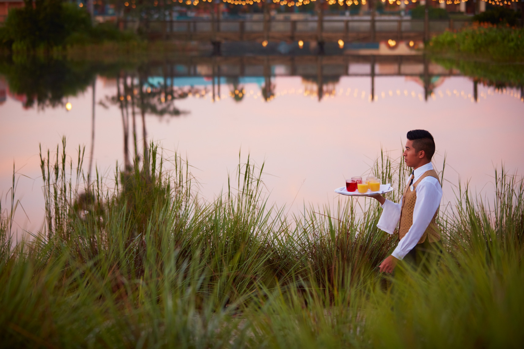 Waiter in white shirt carrying food tray along garden path at dusk by the lagoon