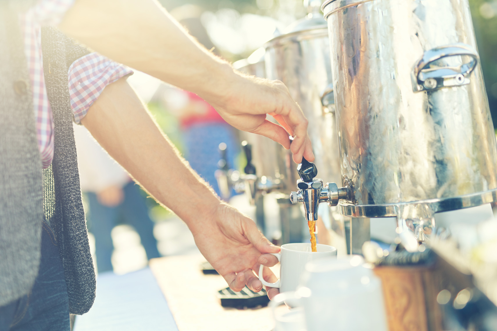 man dispensing coffee into a white mug at an outdoor event San Francisco lifestyle photographer