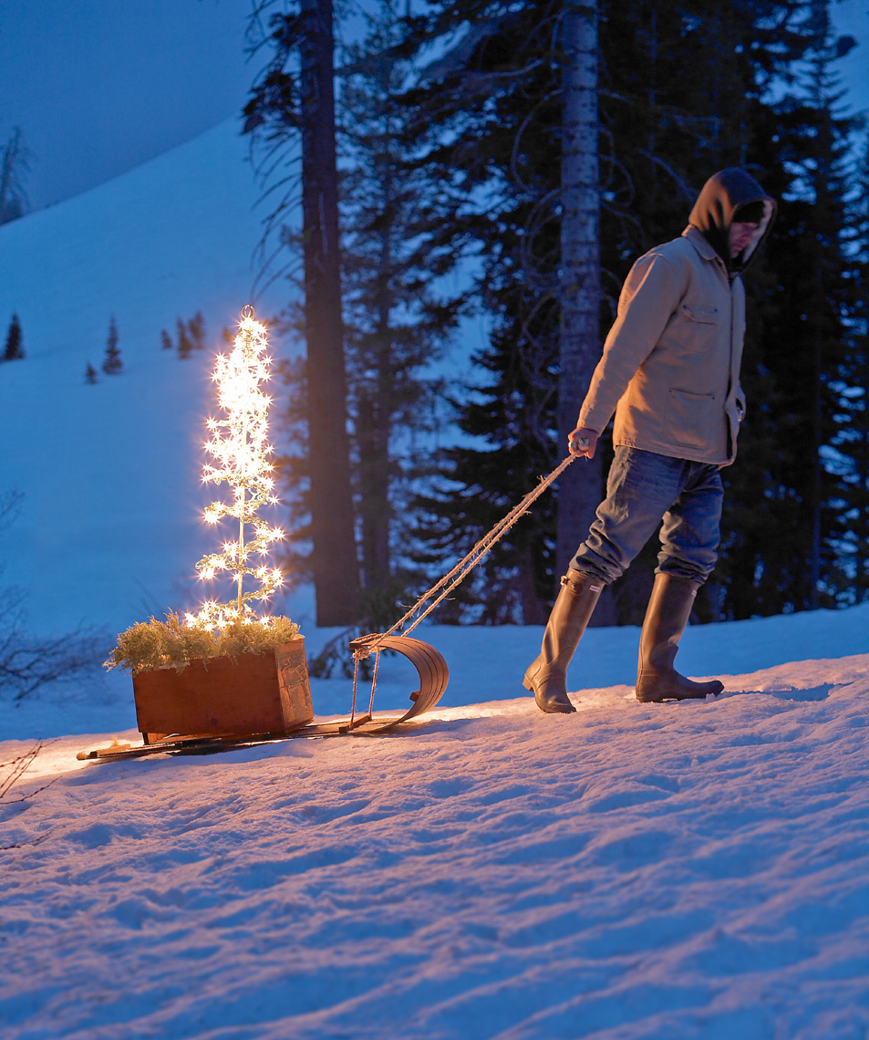 Man pulling sled up hill in snow with lit holiday tree on sled