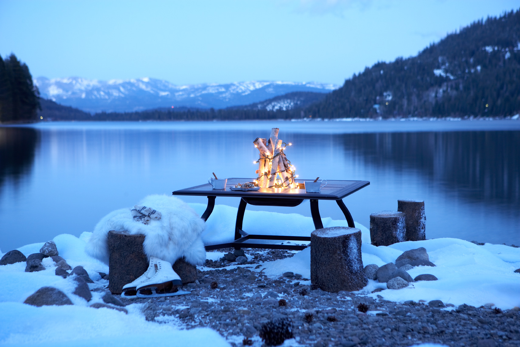 fire bowl with logs and holiday lights in snow on the shore of a mountain lake at dusk with ice skates
