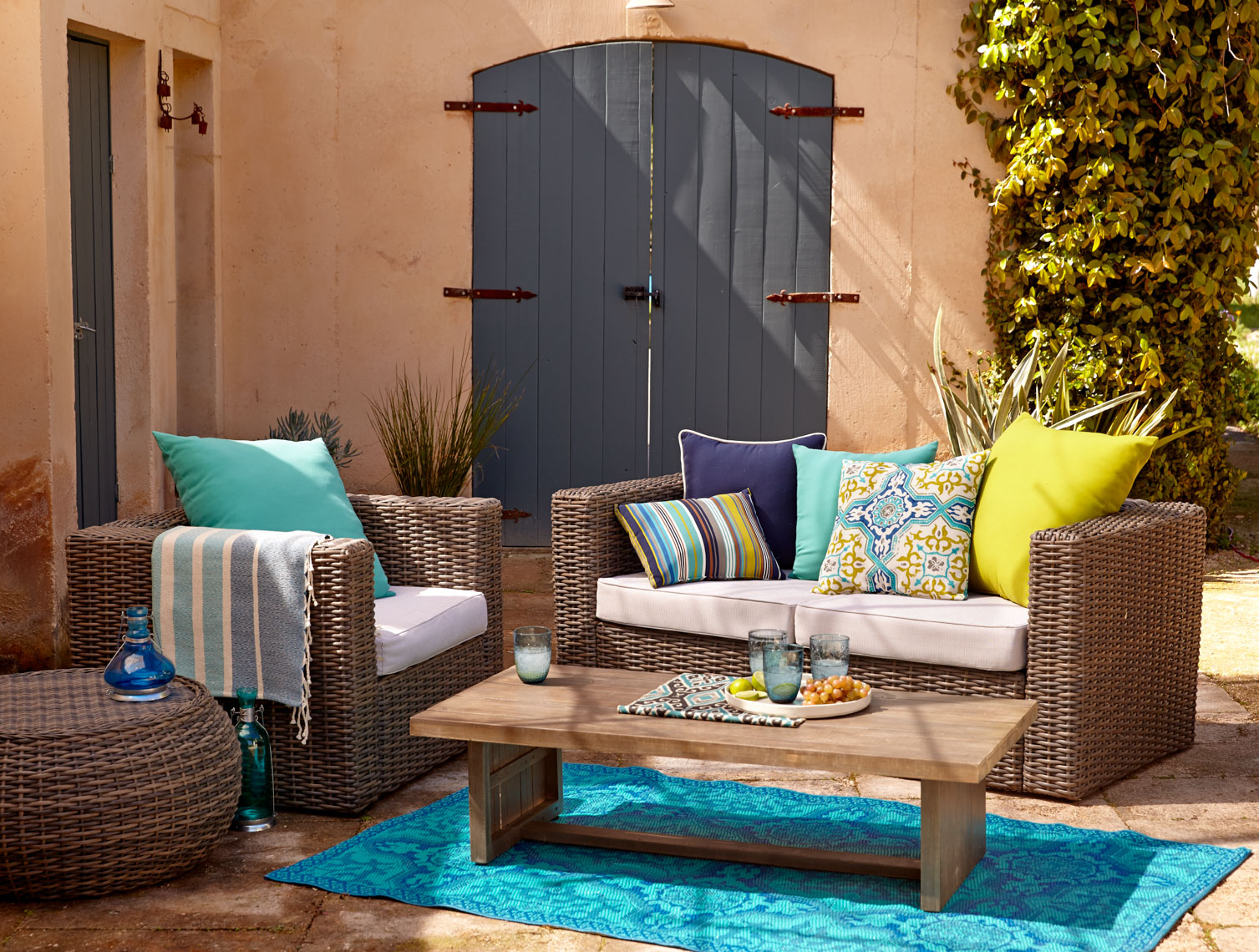 Brown Wicker outdoor furniture set with colorful cushions on blue rug in courtyard