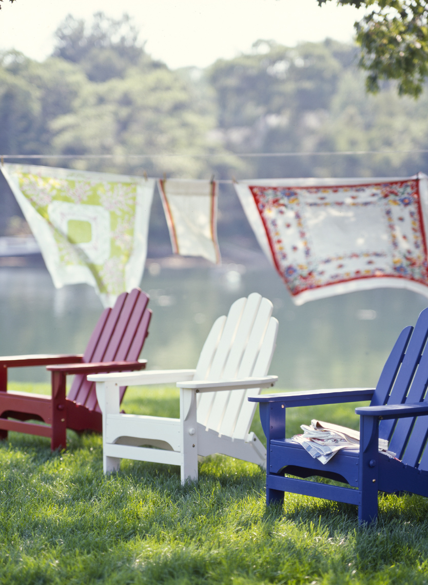 Red white and blue adirondack chairs with table cloths blowing behind