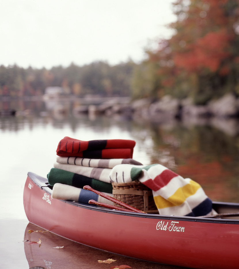 red canoe on still lake with stack of colorful towels