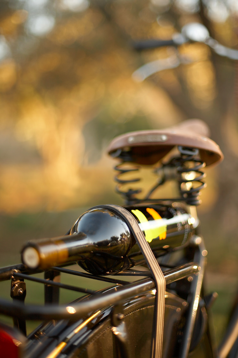bottle of red wine strapped onto old bicycle outside