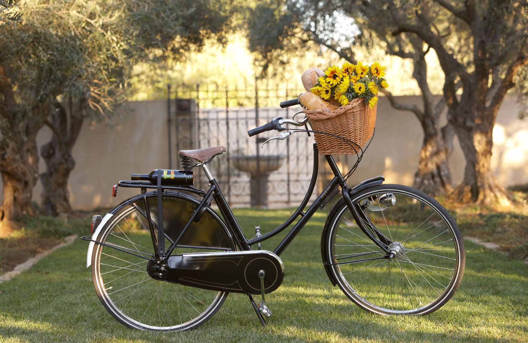 Old fashioned black bike with wicker basket of flowers