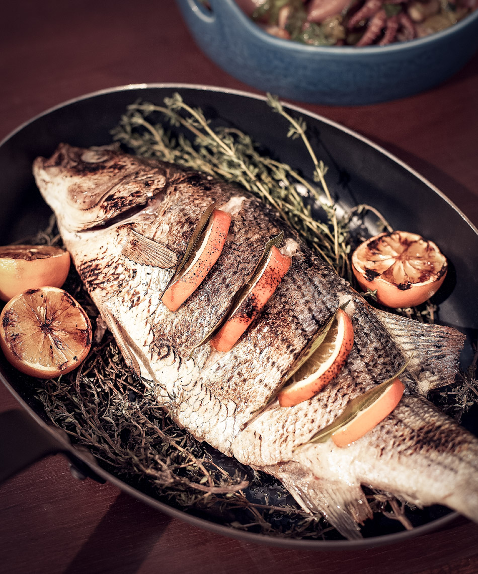 whole cooked fish stuffed with citrus slices and herbs