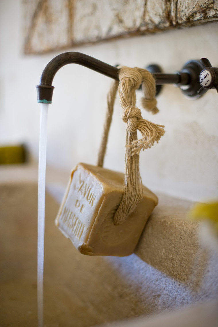 metallic sink pouring water with bar of soap wrapped around with rope