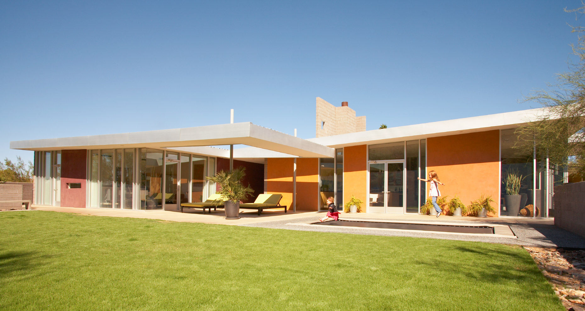 Low modern orange and white desert home with green grass and blue sky San Francisco architectural photographer