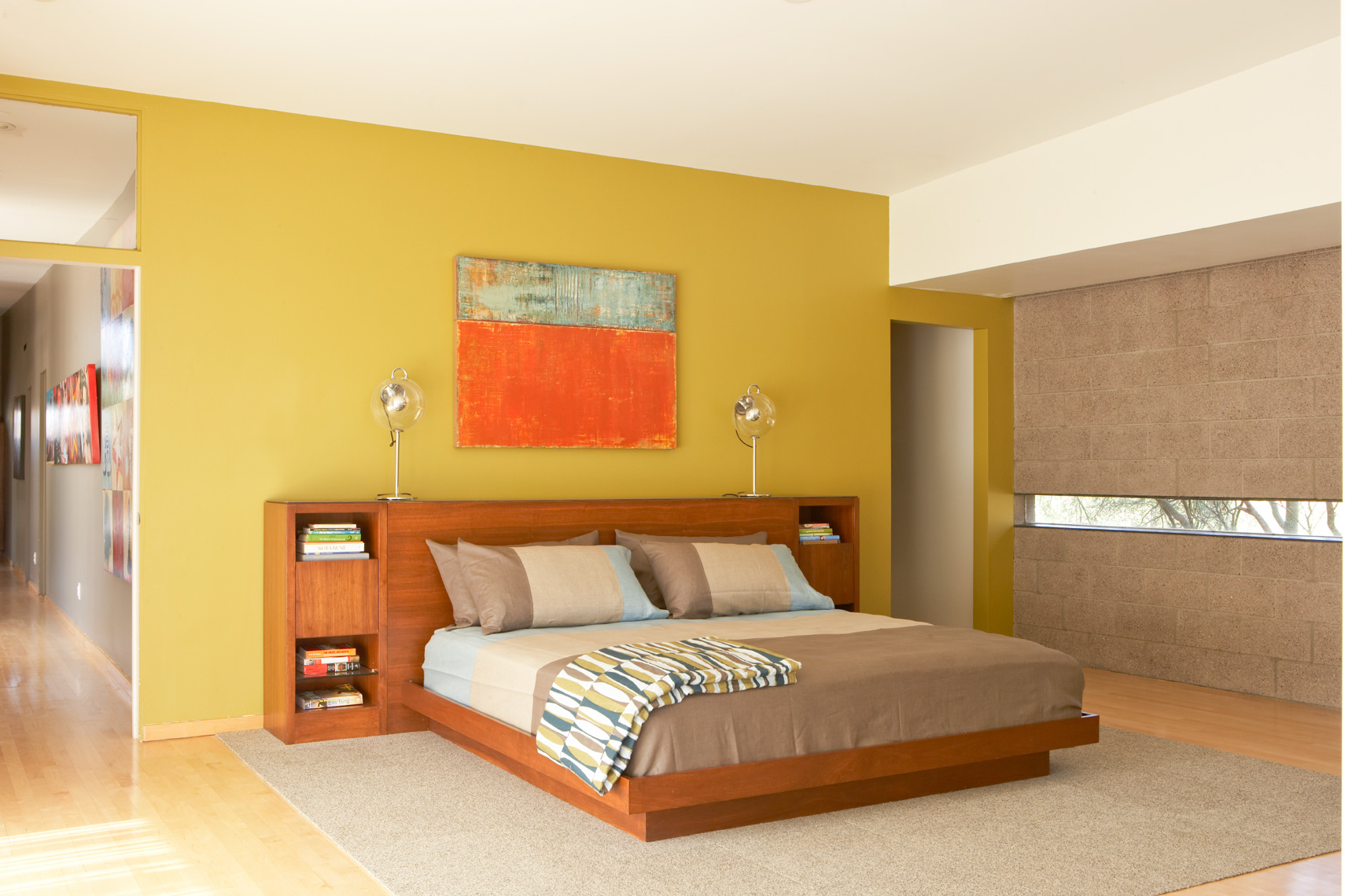 bedroom interior with mustard wall and taupe bedding
