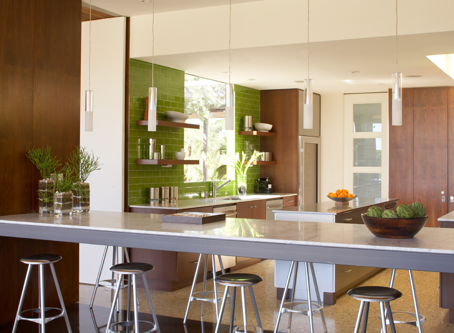 green-tiled kitchen interior with long white counter and stools