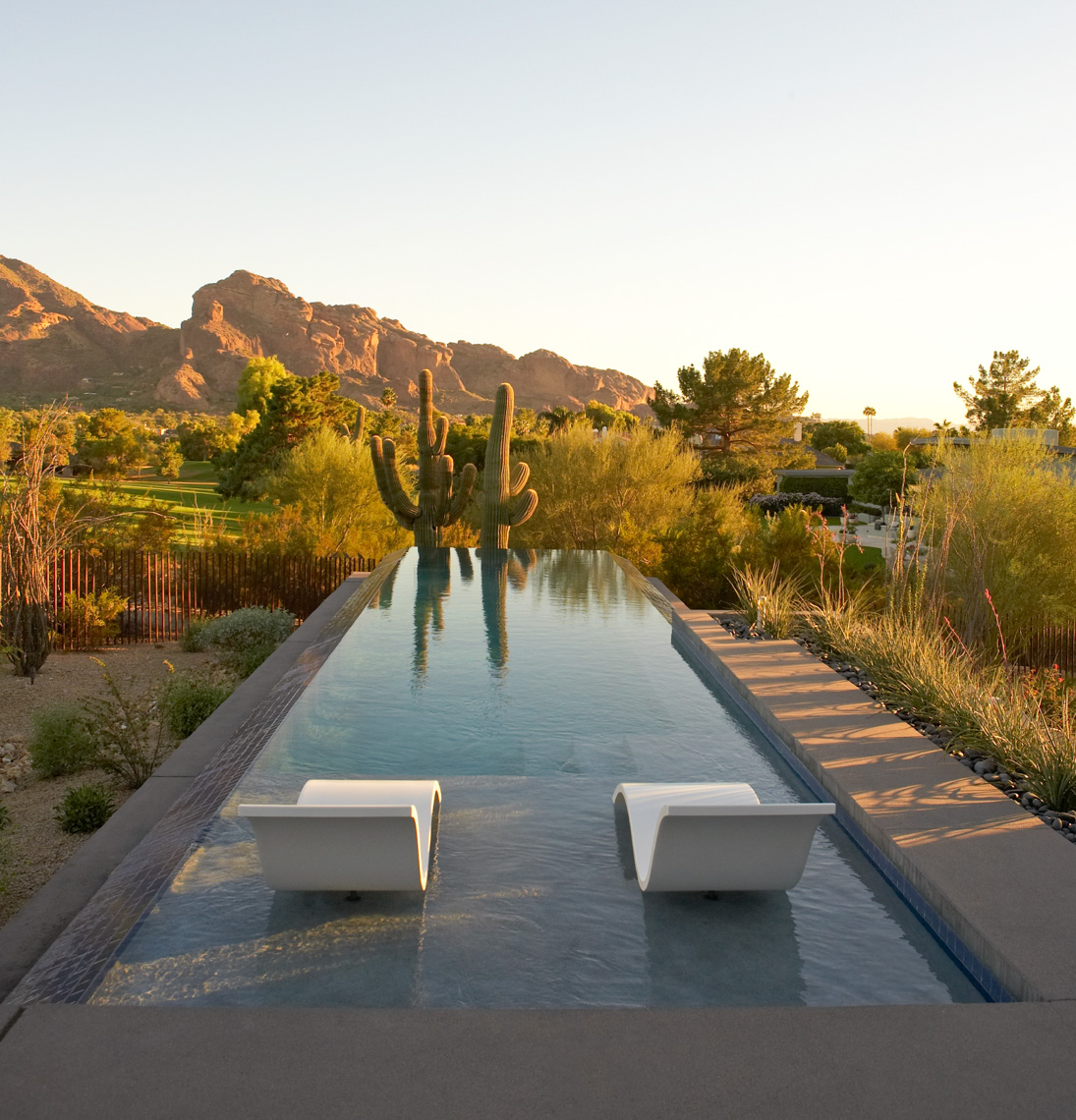 infinity pool with chic white lounge chairs overlooking golf course and desert mountains