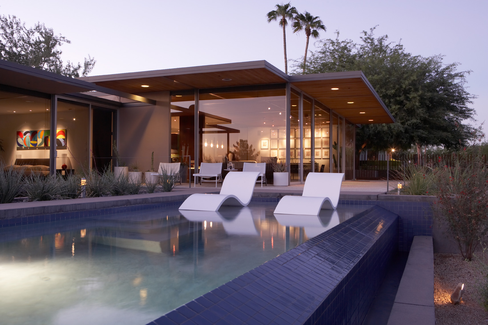 White modern chairs in blue pool at dusk in the desert with modern home and palm trees behind