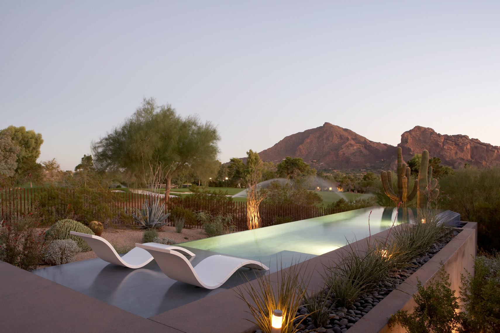 White modern chairs in blue pool at dusk in the desert with mountains behind