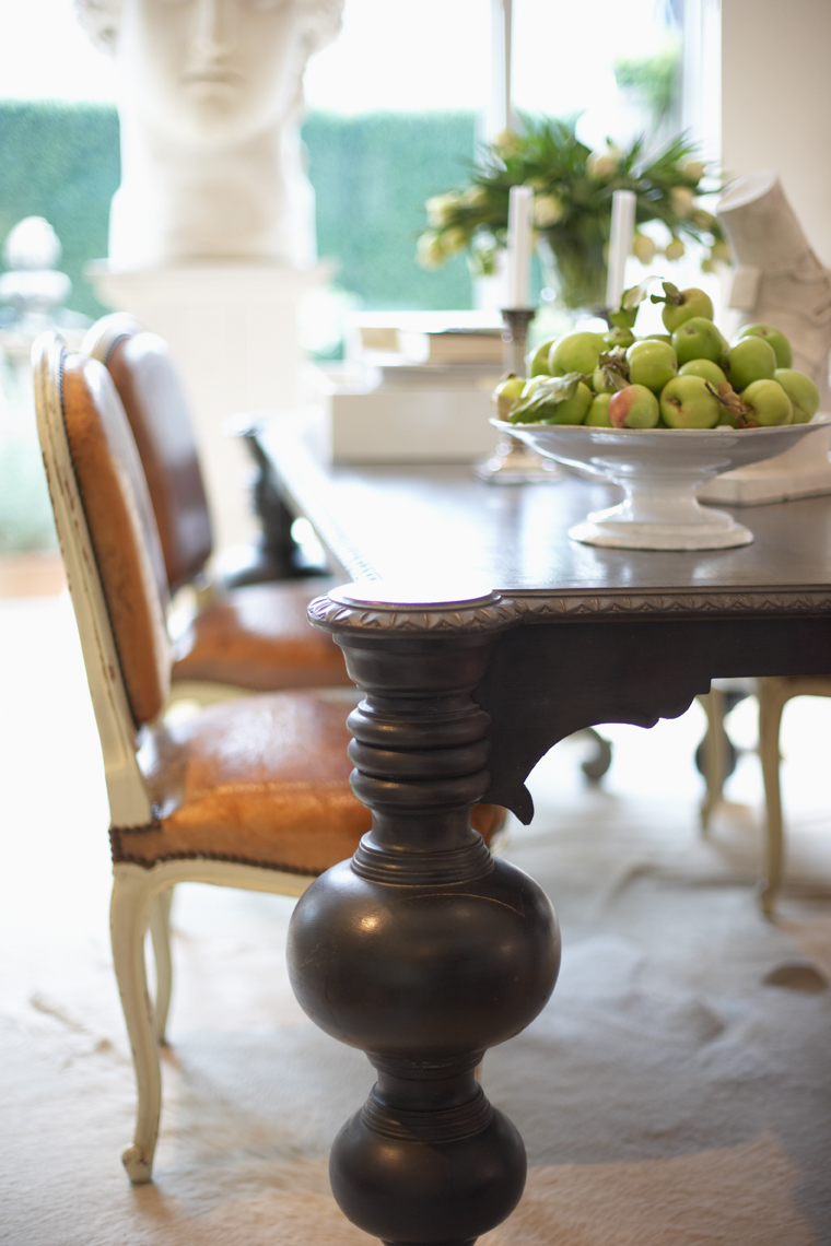 detail of black dining room table leg and bowl of pears on table