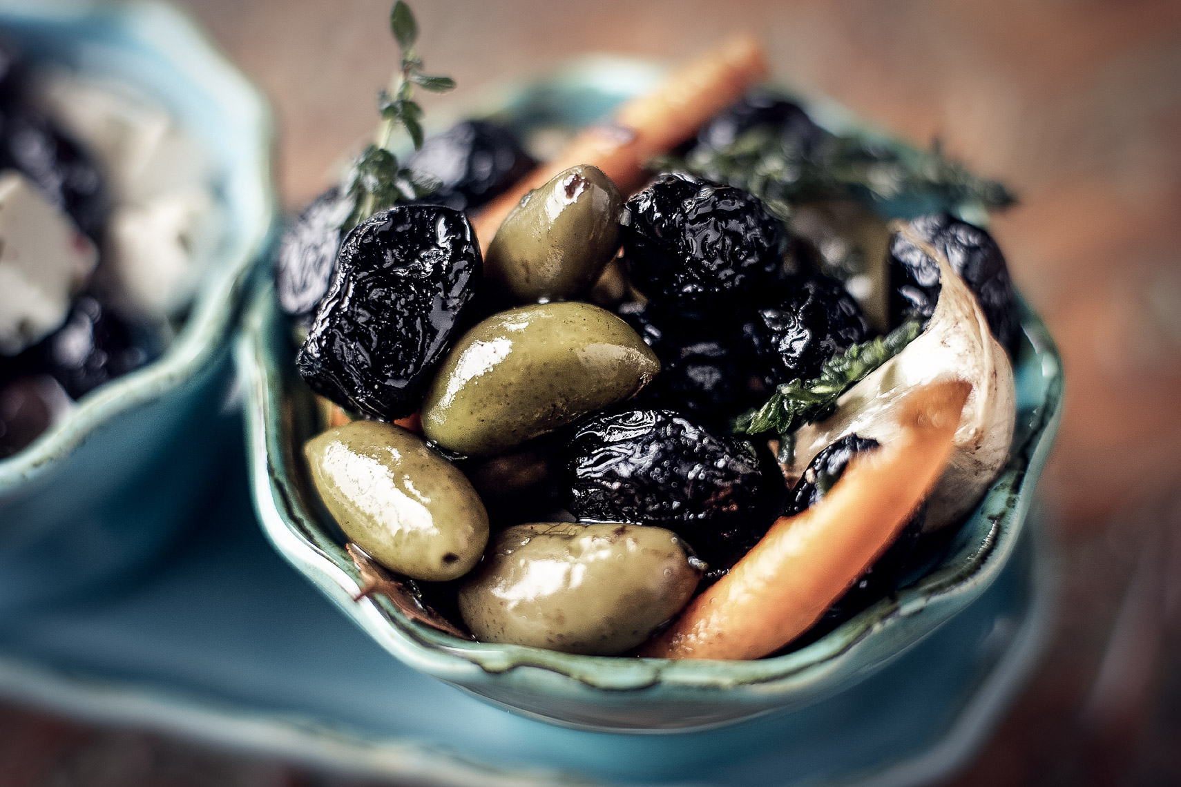 black and green artisanal olives in blue bowl