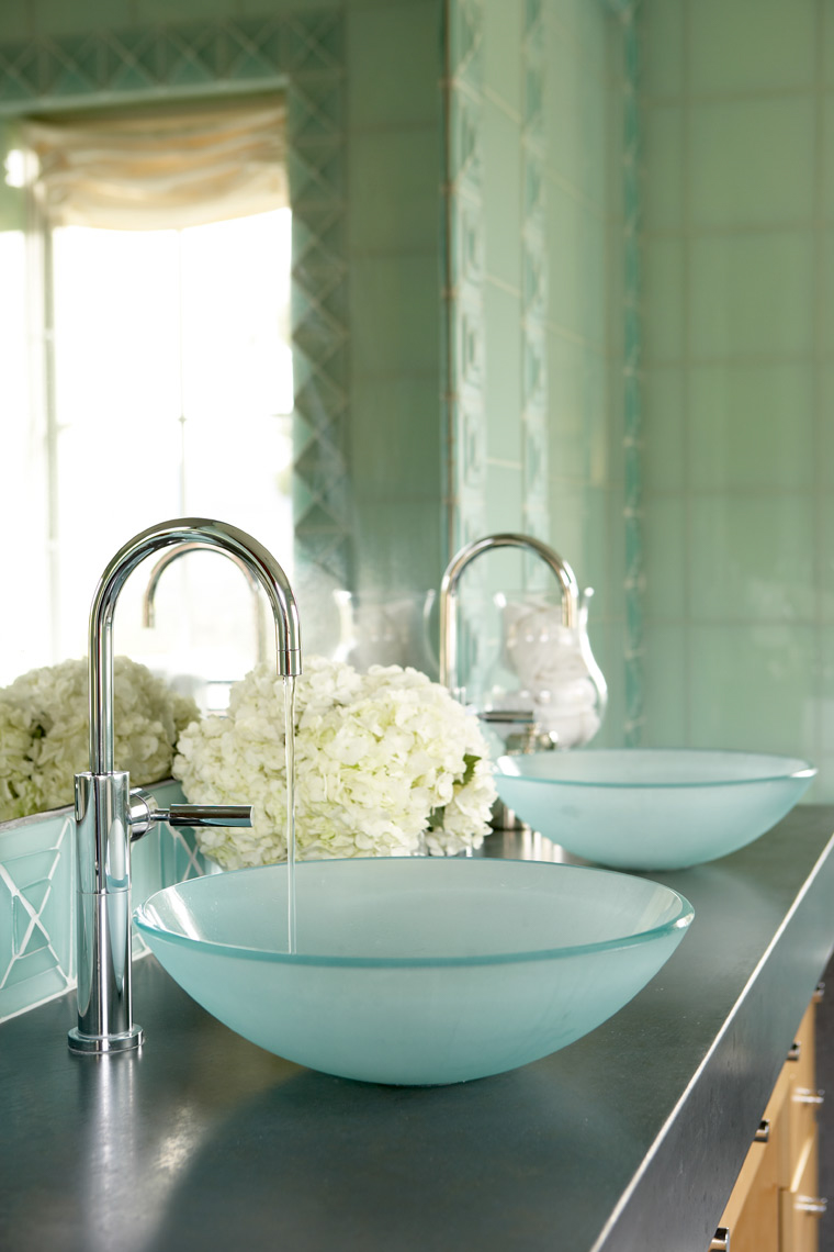 bathroom with metal sinks pouring into blue sea glass bowls with teal walls