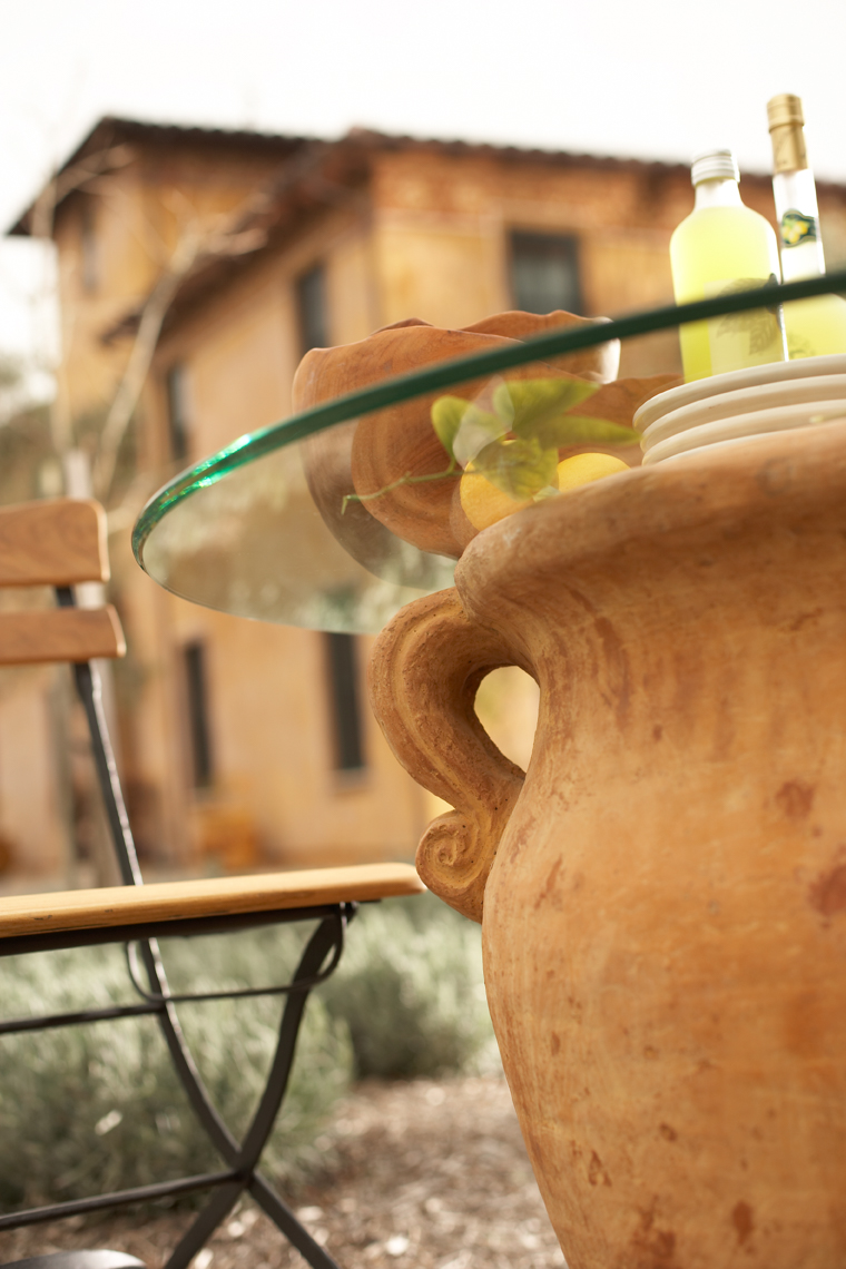 Detail of glass tabletop set on large terra cotta pot with cafe chair