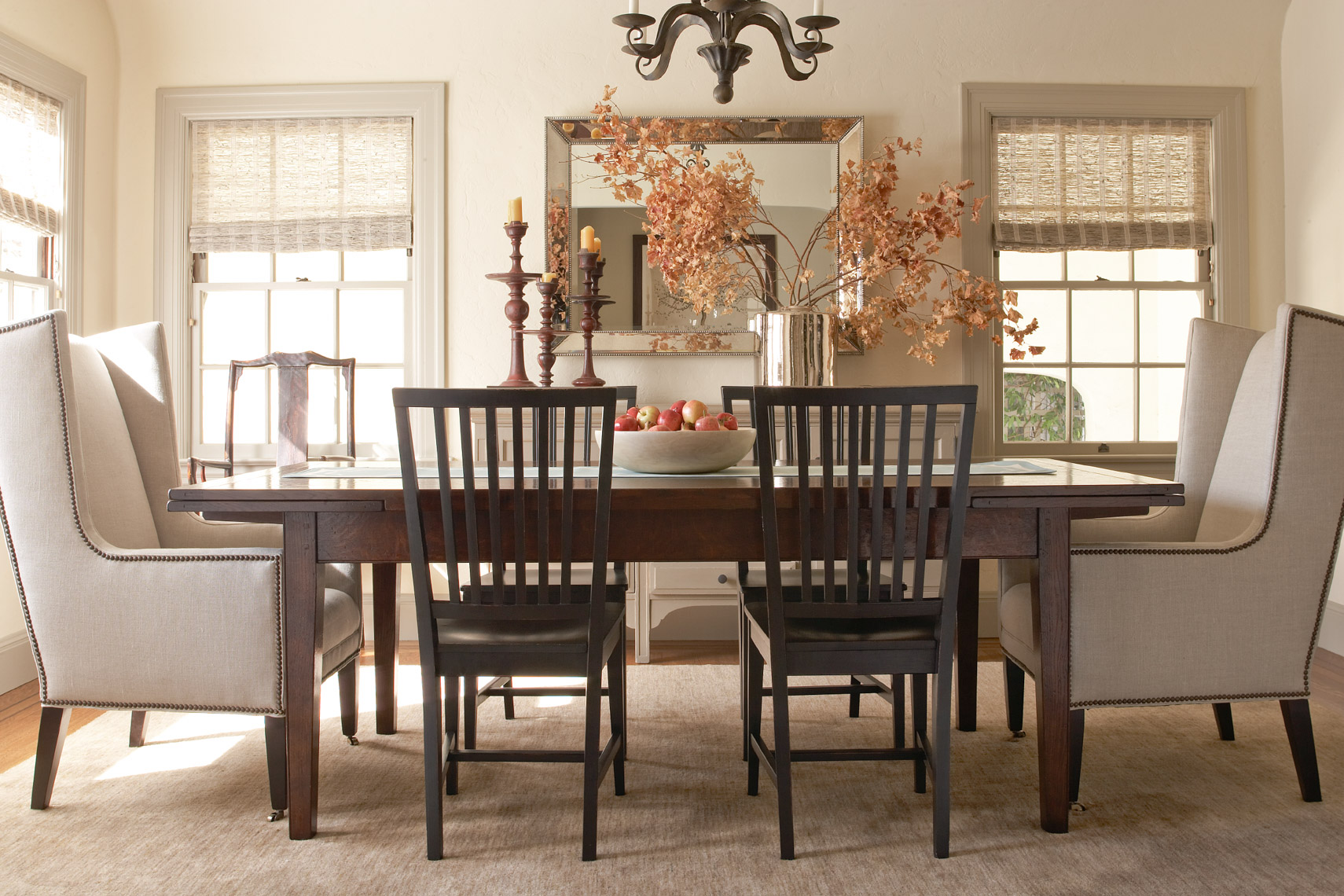 wooden dining table with 2 grey armchairs and black dinner chairs