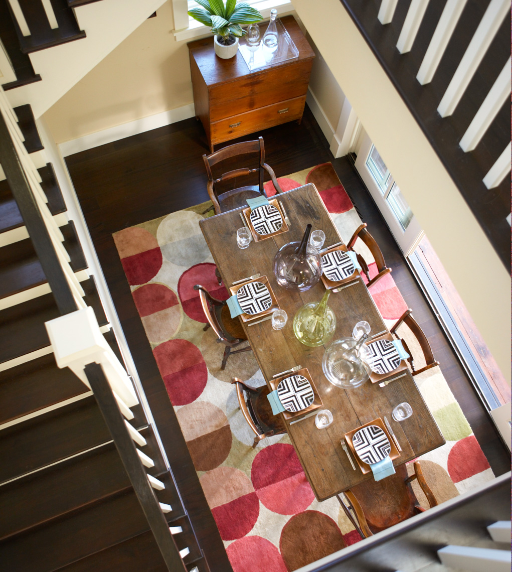 view of dining table from above showing black and white staircase and colorful rug