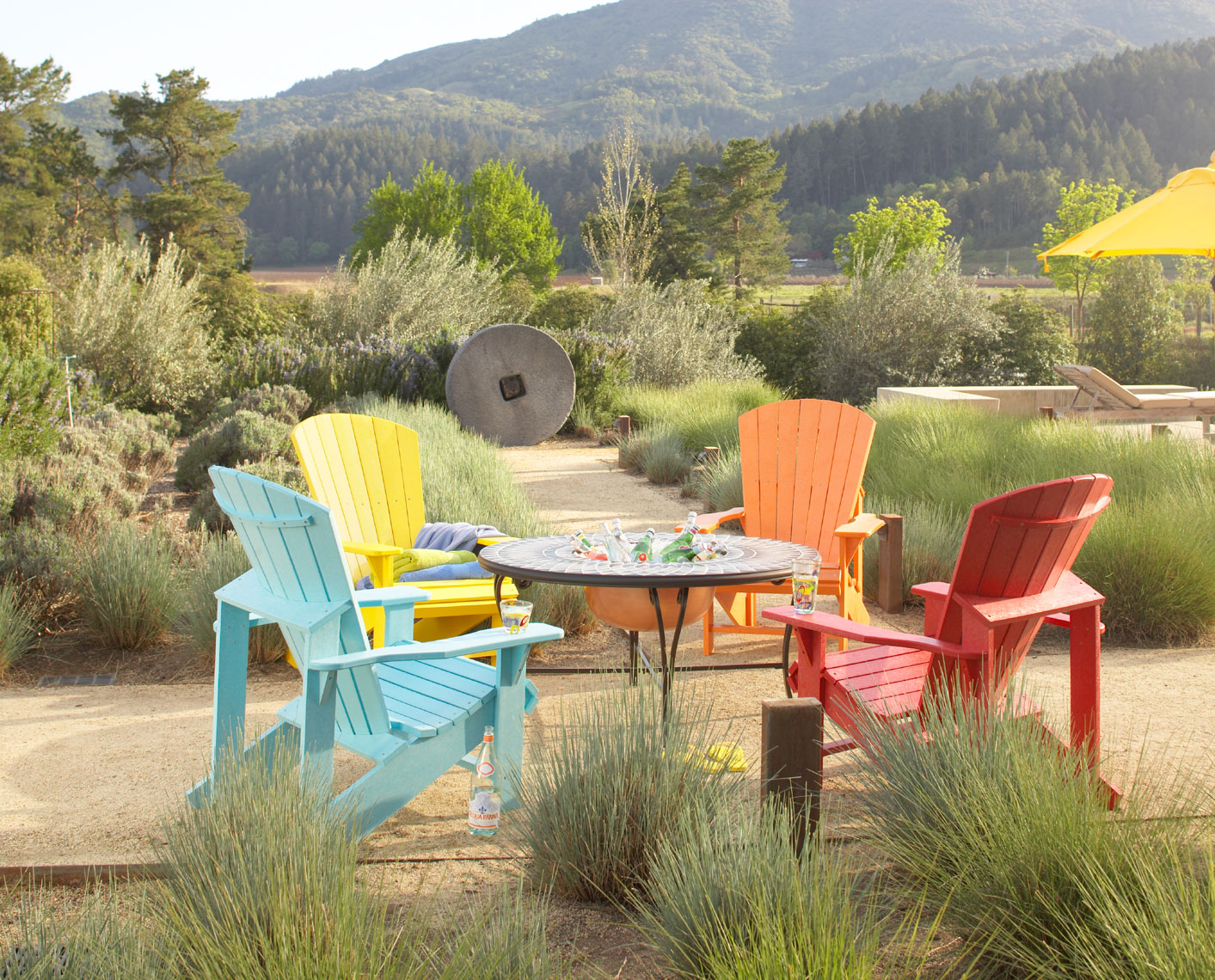 Collection of colorful adirondack chairs around fire bowl in wine country setting