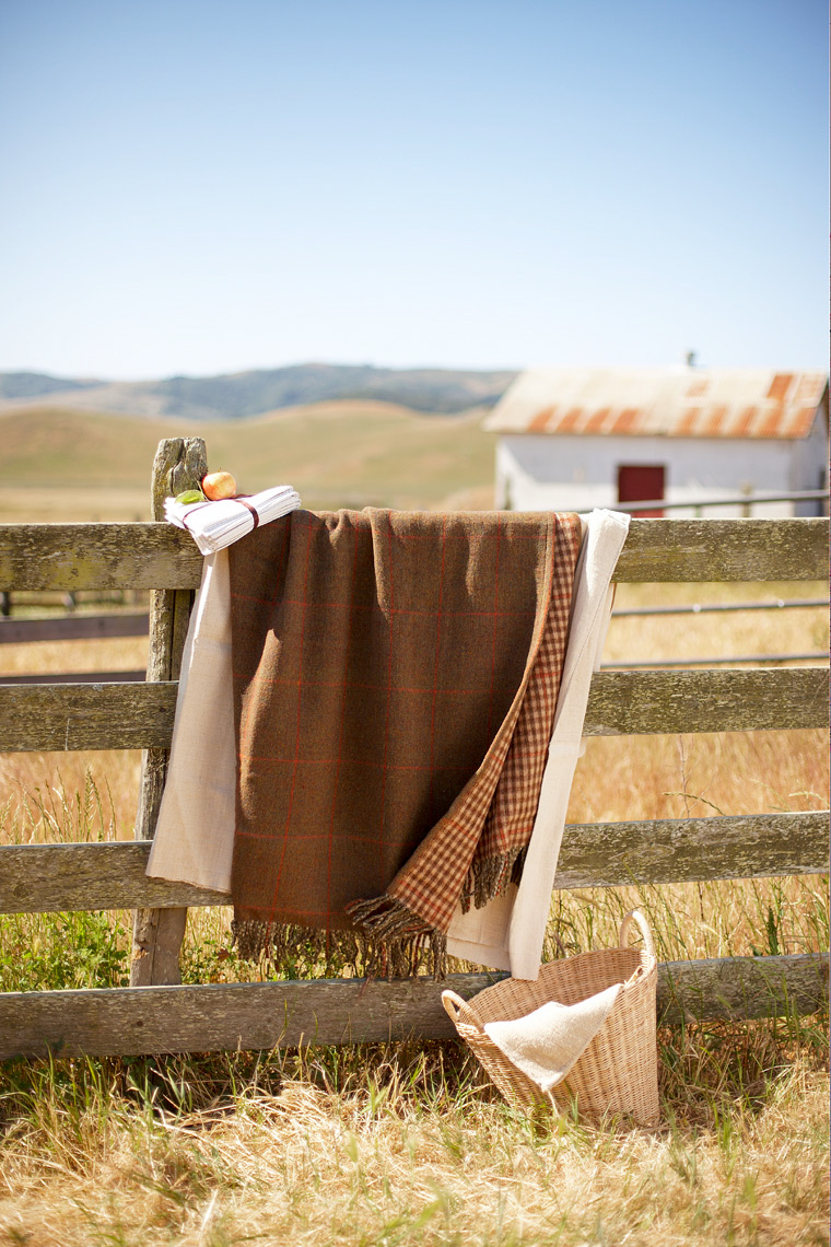 brown and white quilts draped over barn fence with woven basket and ranch-style outdoors