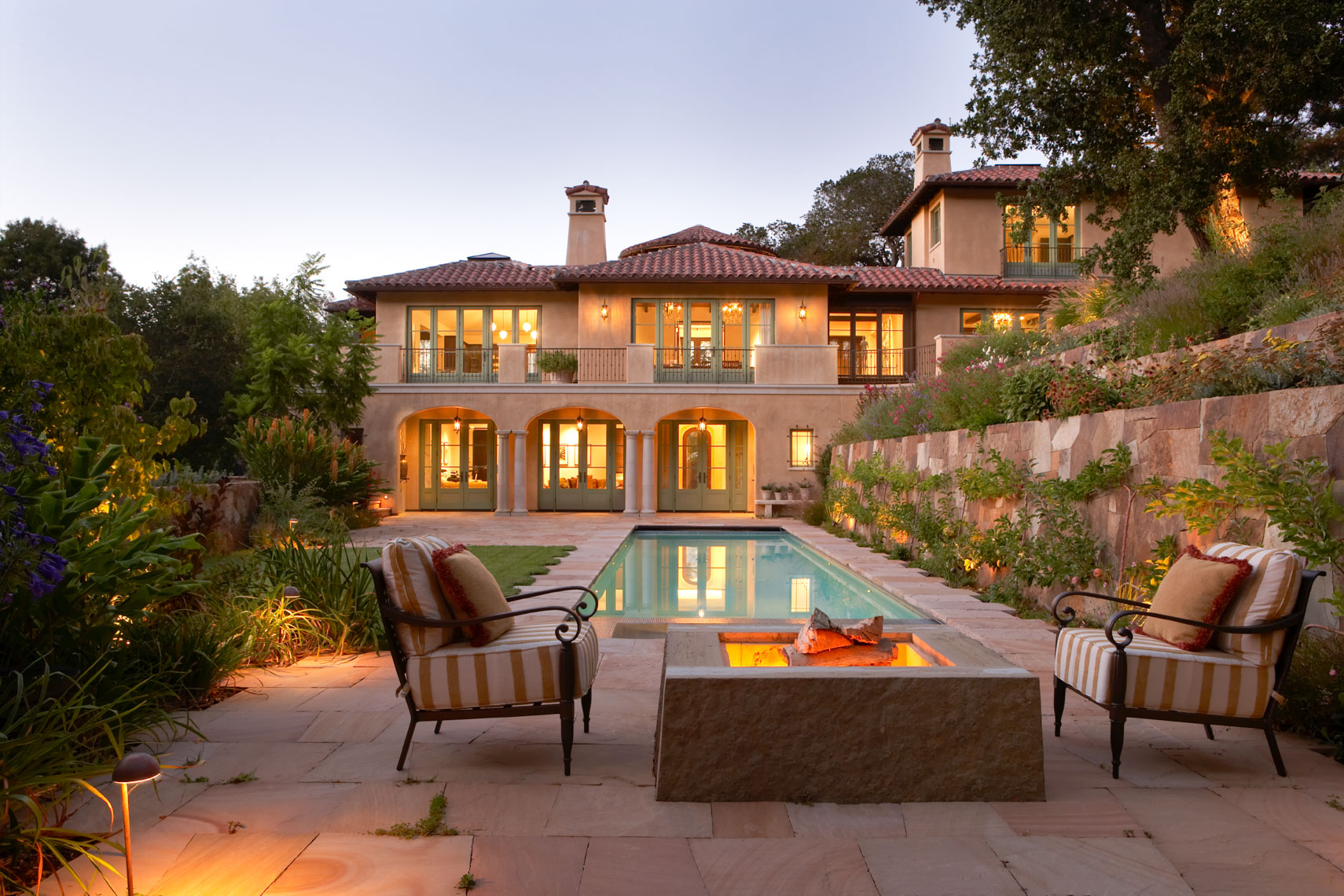Outdoor seating around fire bowl on stone patio with pool and hotel