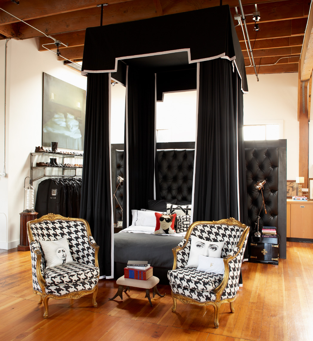 bedroom with large black canopy over black and white bed and 2 gold framed chairs