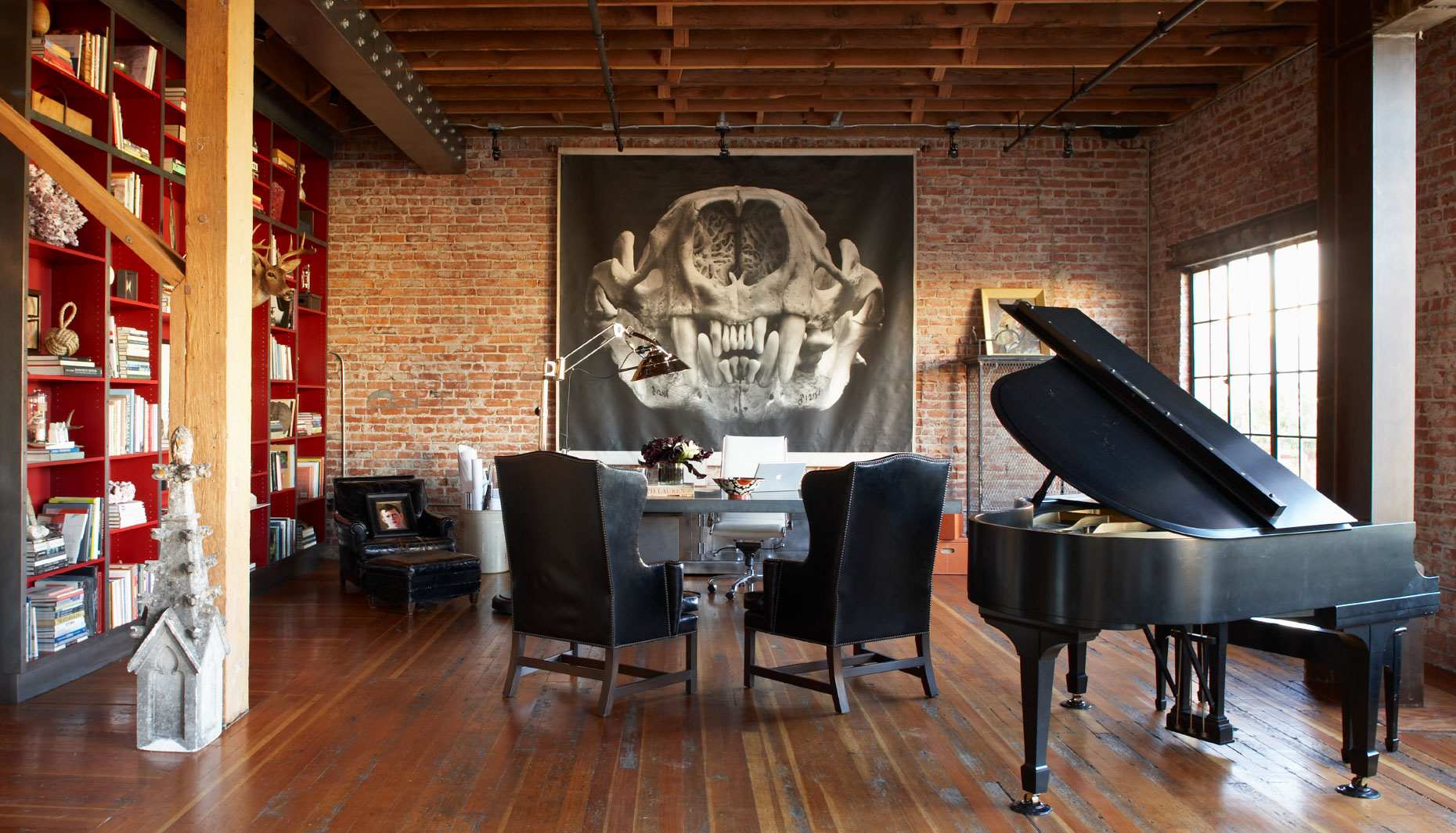 living room and office space with grand piano and large hanging black and white photograph on red brick wall