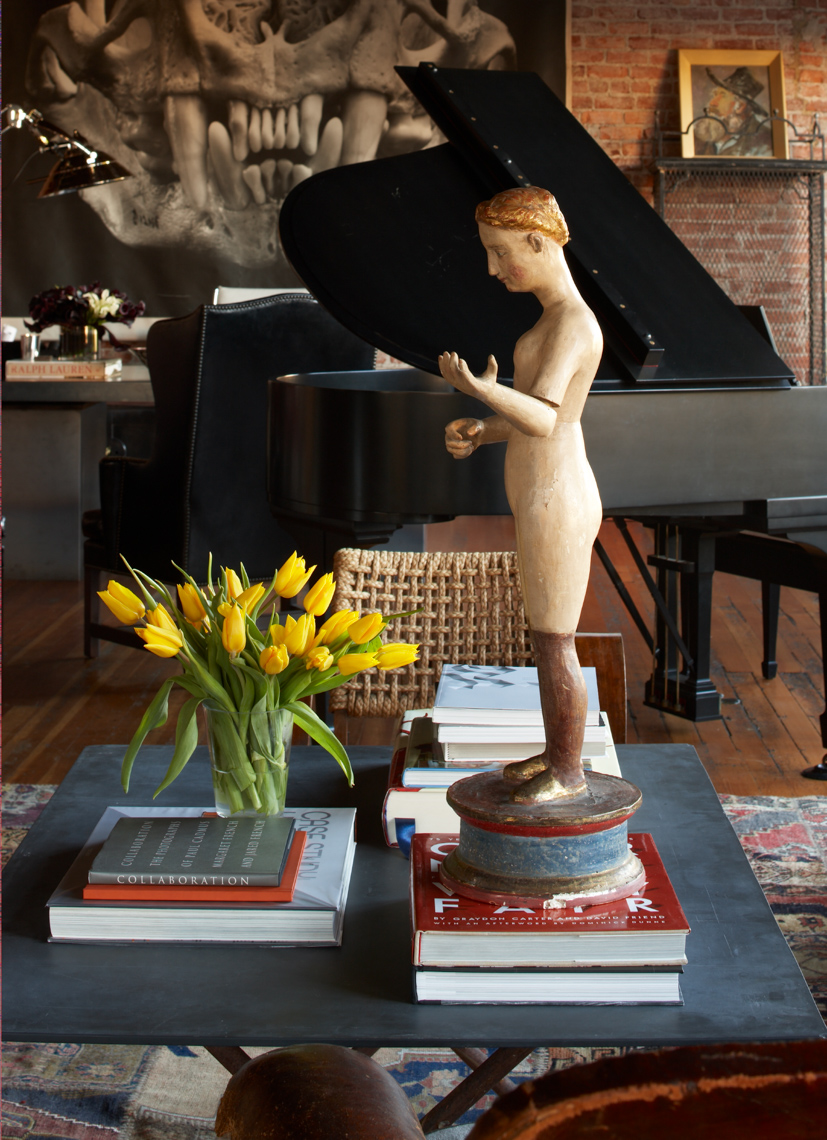 living room interior with small sculpture on stack of books and grand piano