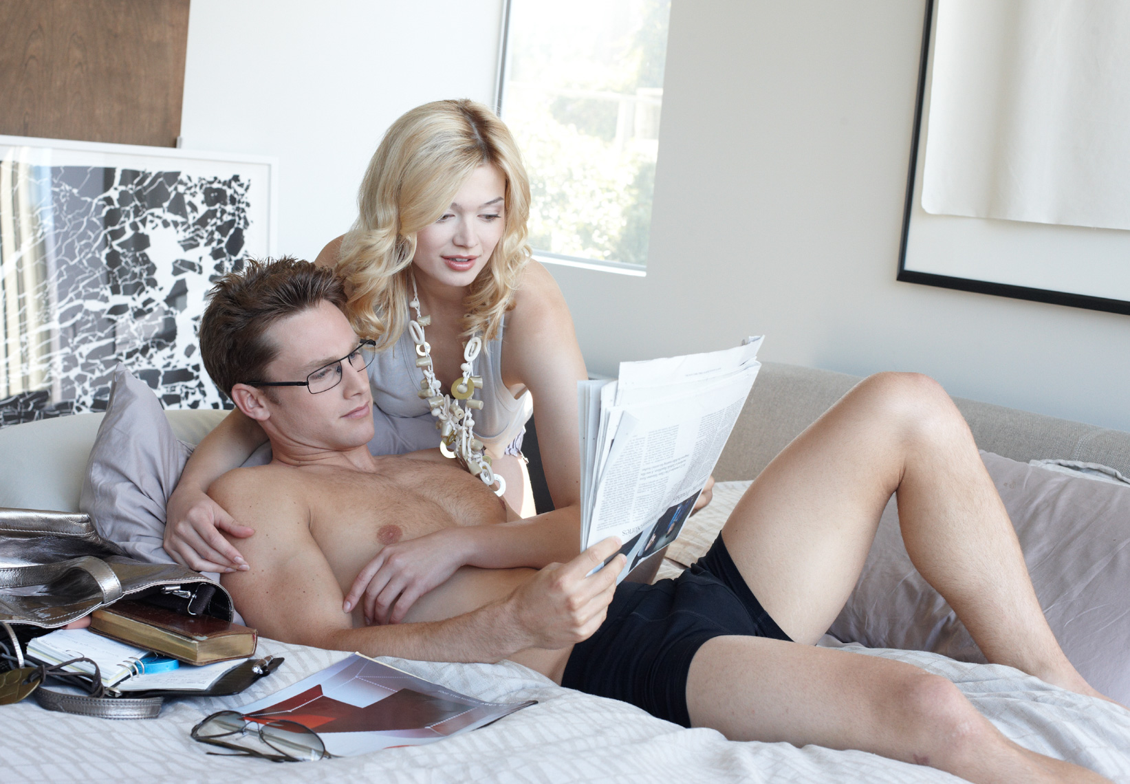 Blond woman leans over a man wearing black shorts with magazines on the bed