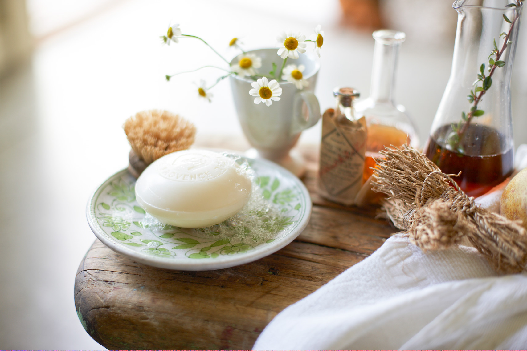 white bar of soap on green floral dish with daisies in white mug on wooden surface San Francisco product photographer