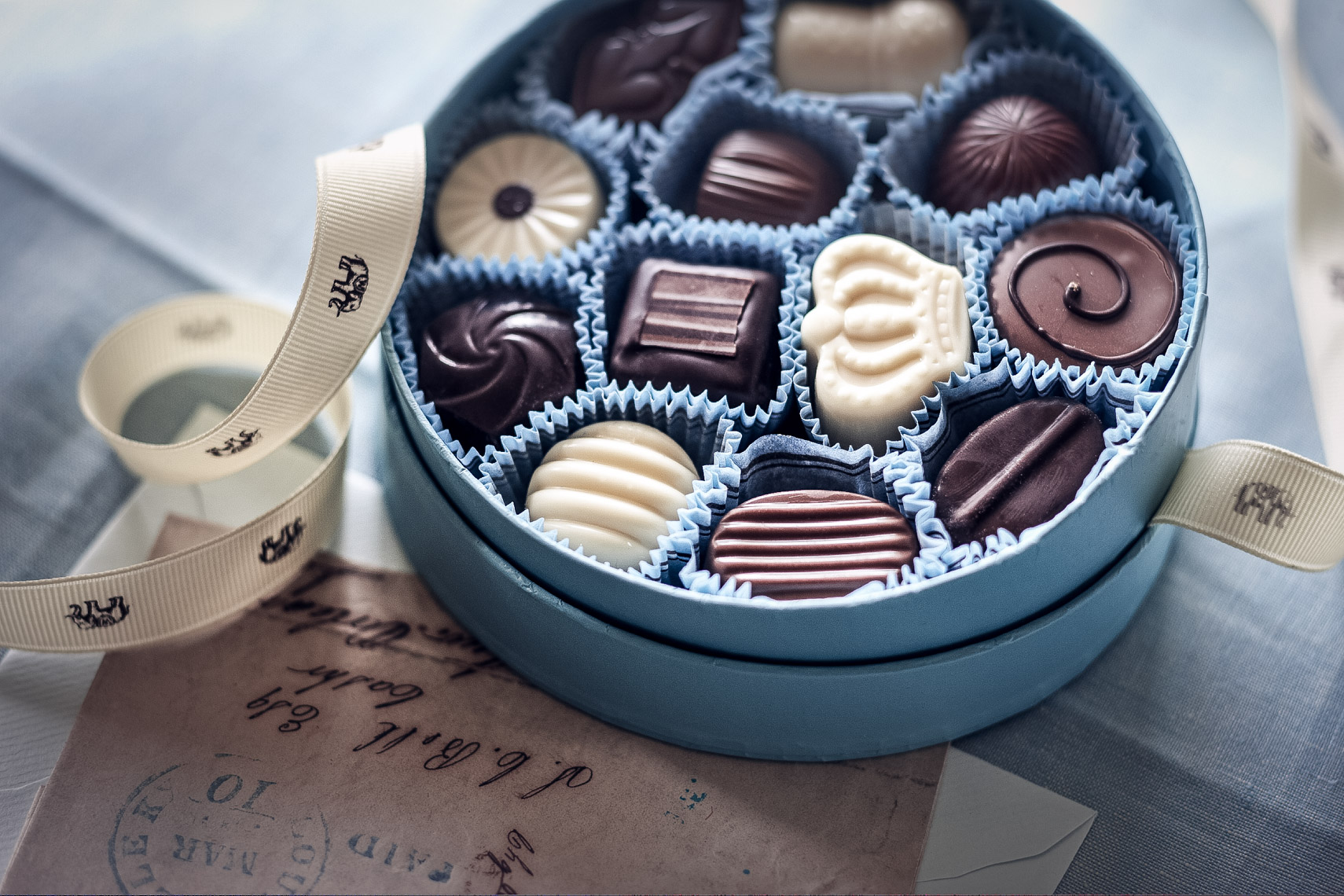 round blue open box of chocolates with white ribbon