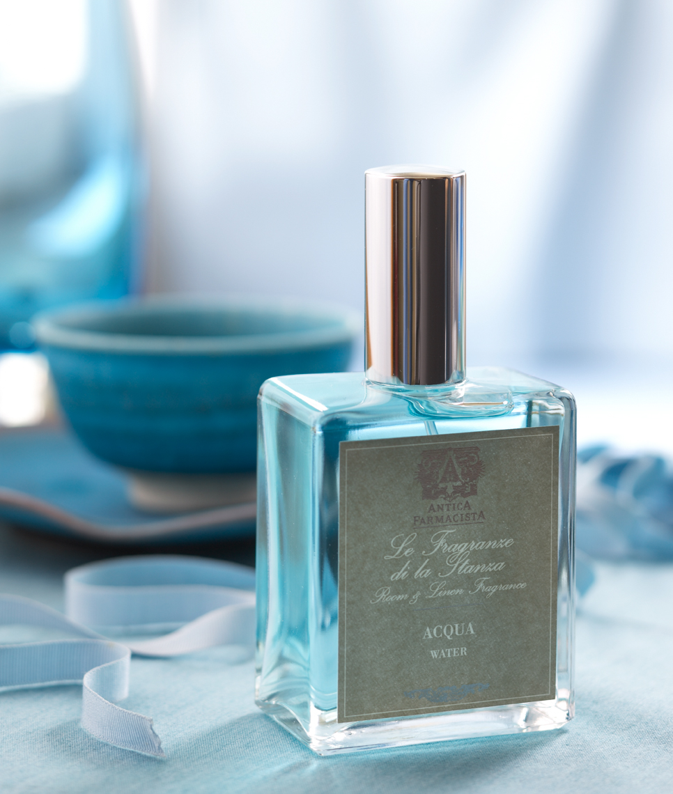 bottle of blue perfume with white ribbon and blue bowl San Francisco product photographer
