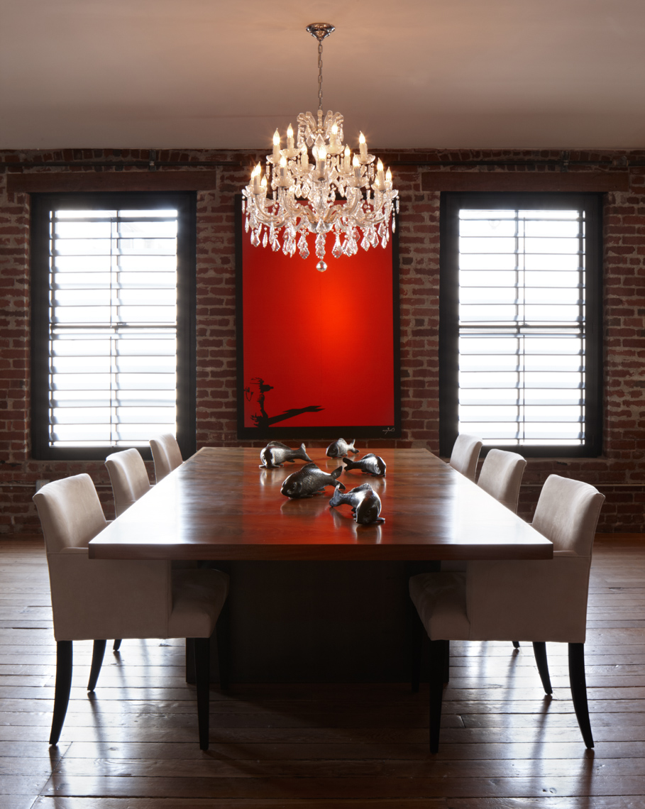 wooden dining table with white chairs and framed red painting on brick wall