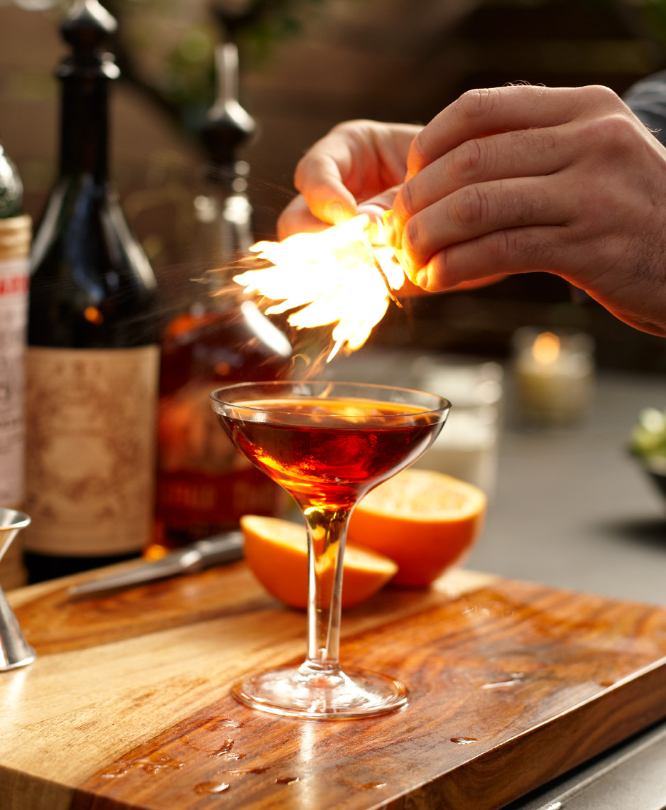 martini glass with flaming drink on cutting board with fresh fruit