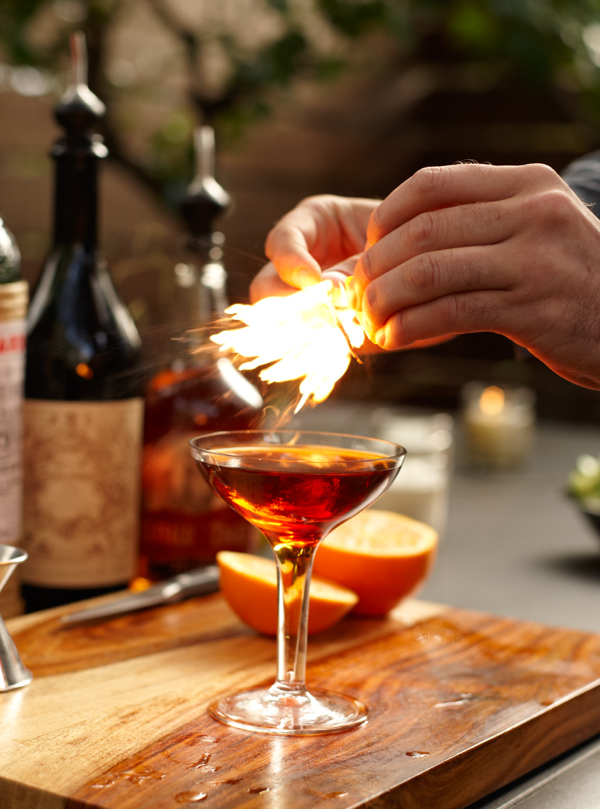bartender with flaming drink in martini glass