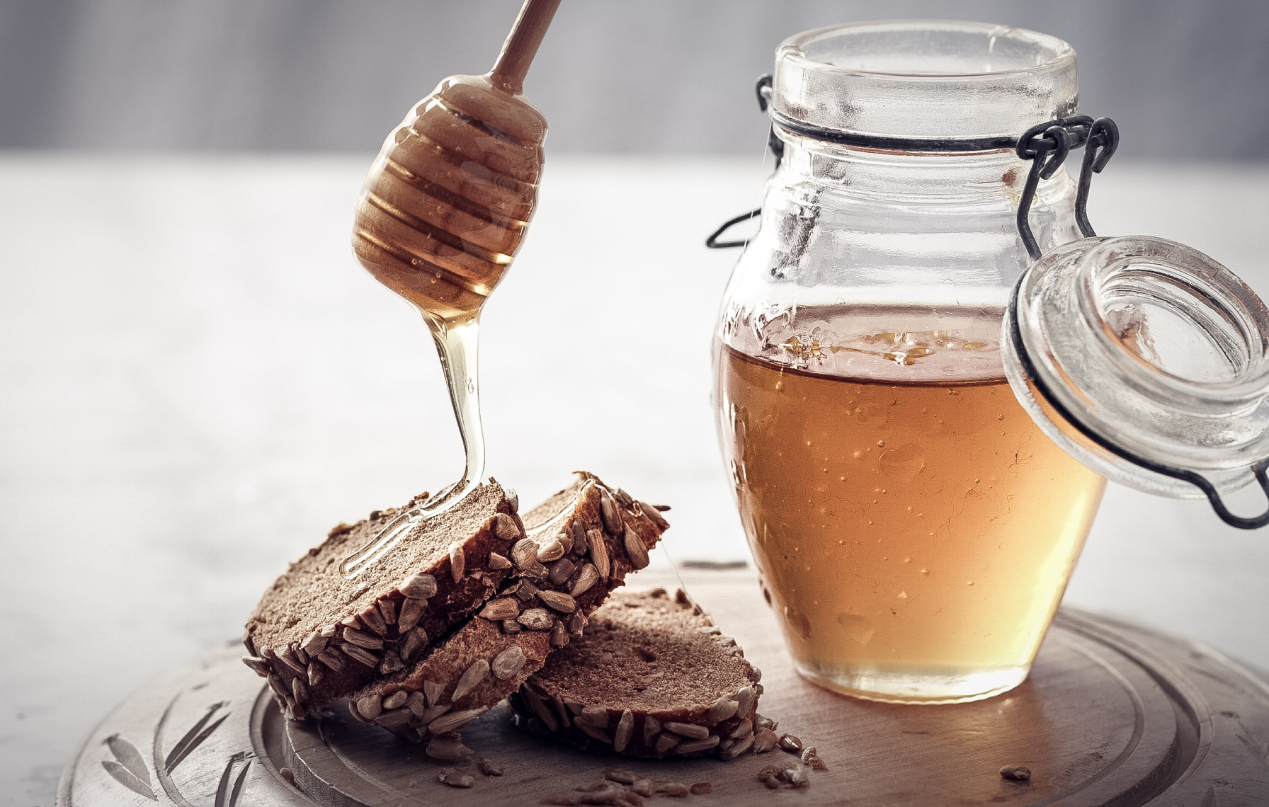 glass jar of honey with honey being drizzled over wheat bread