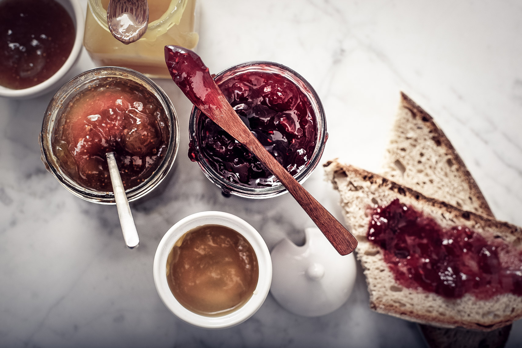 assortment of jams and jelly spread on sliced bread