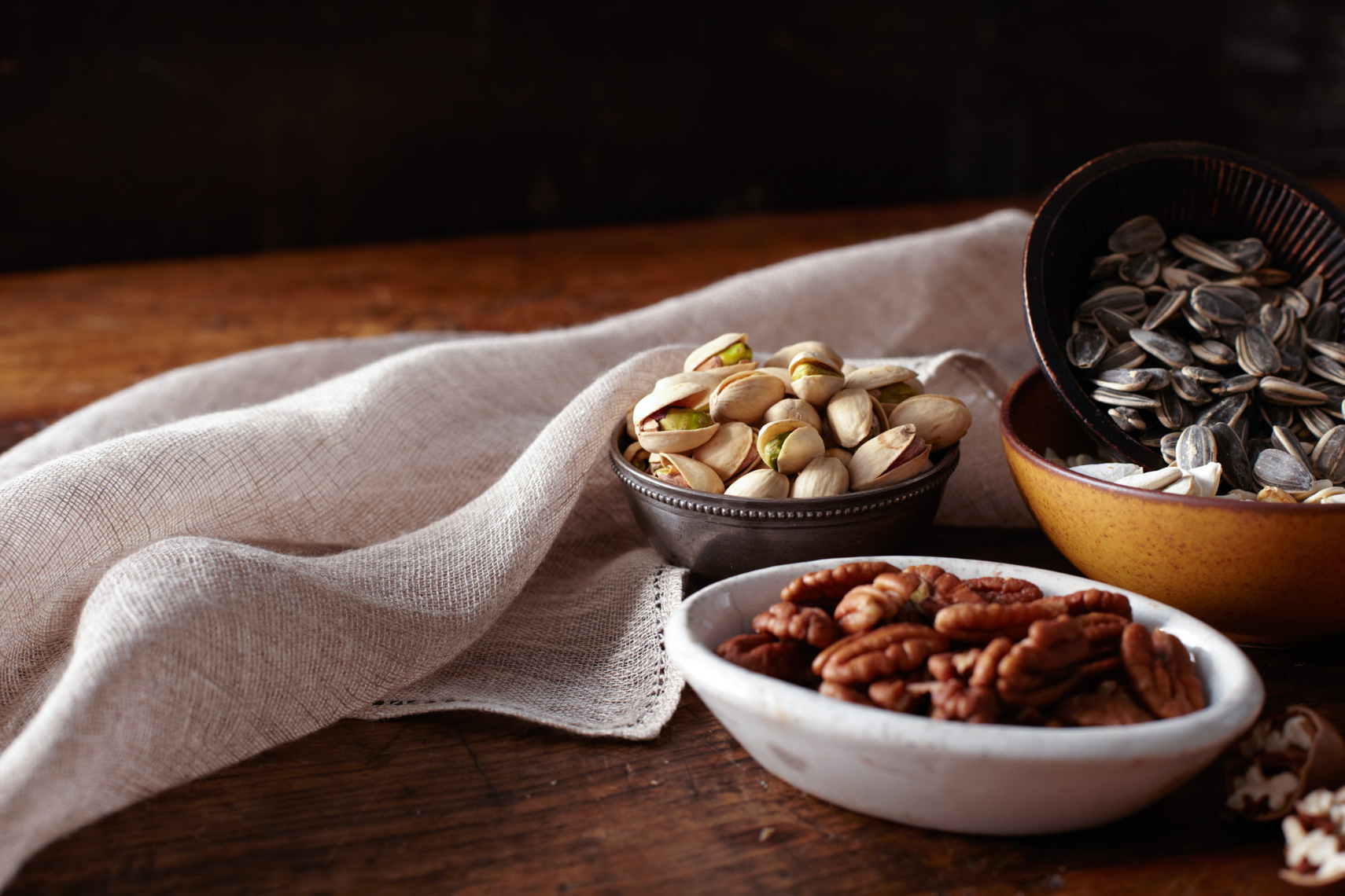 small bowls with pistachios, pecans and sunflower seeds