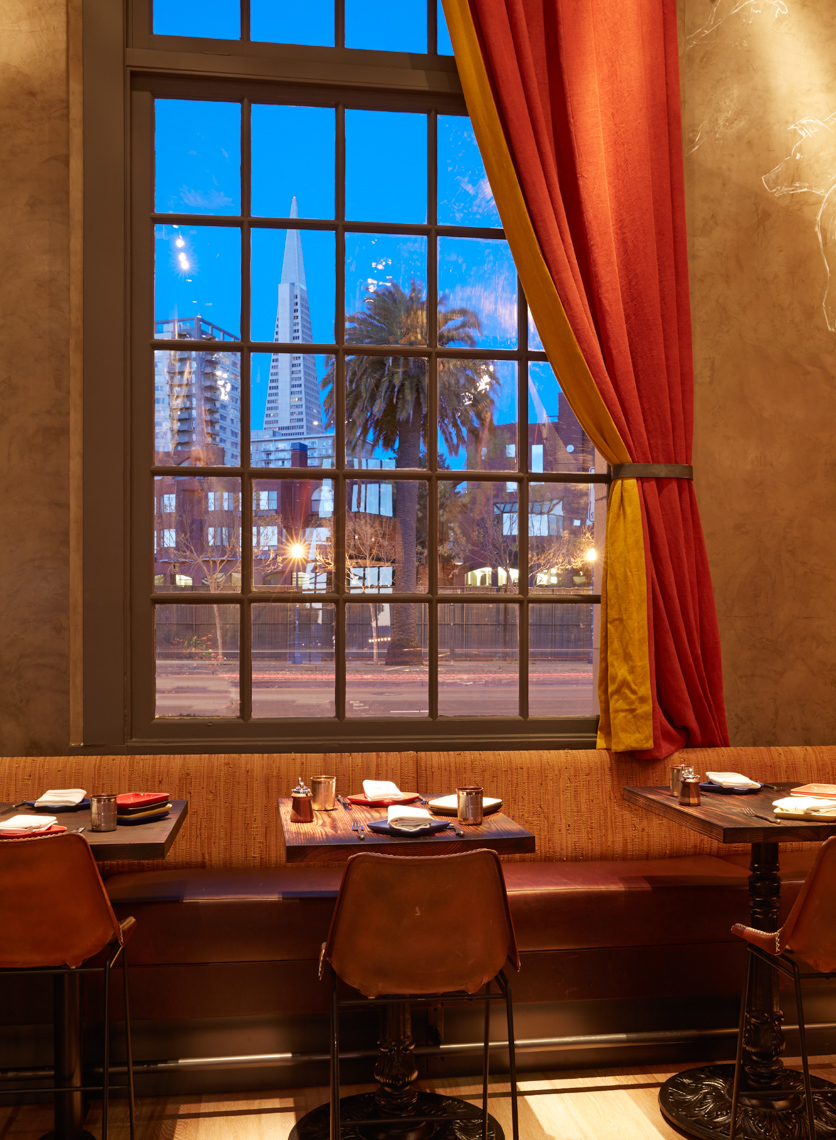 Dusk view of a restaurant table and window with view to San Francisco city behind