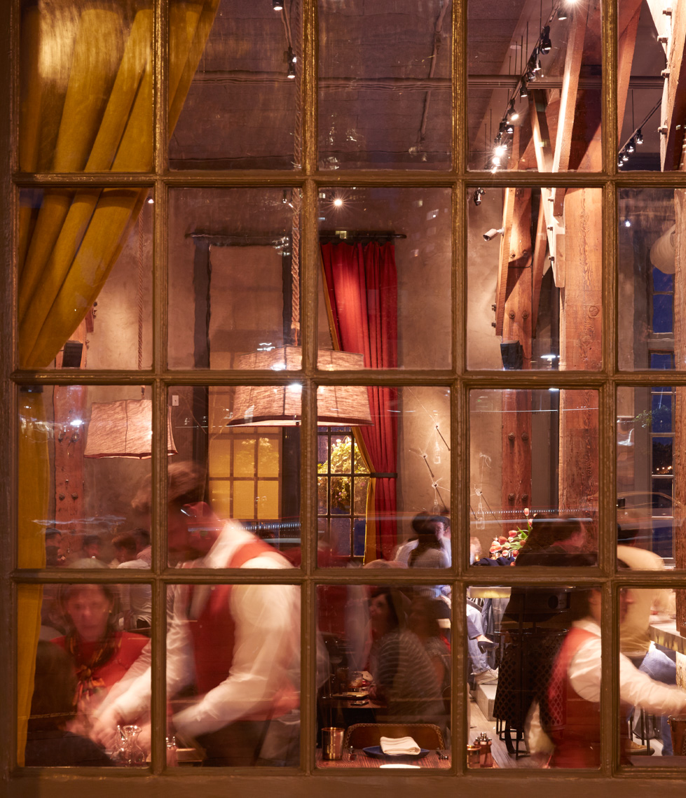 Night time View through a window into a restaurant with waiter serving San Francisco lifestyle photographer