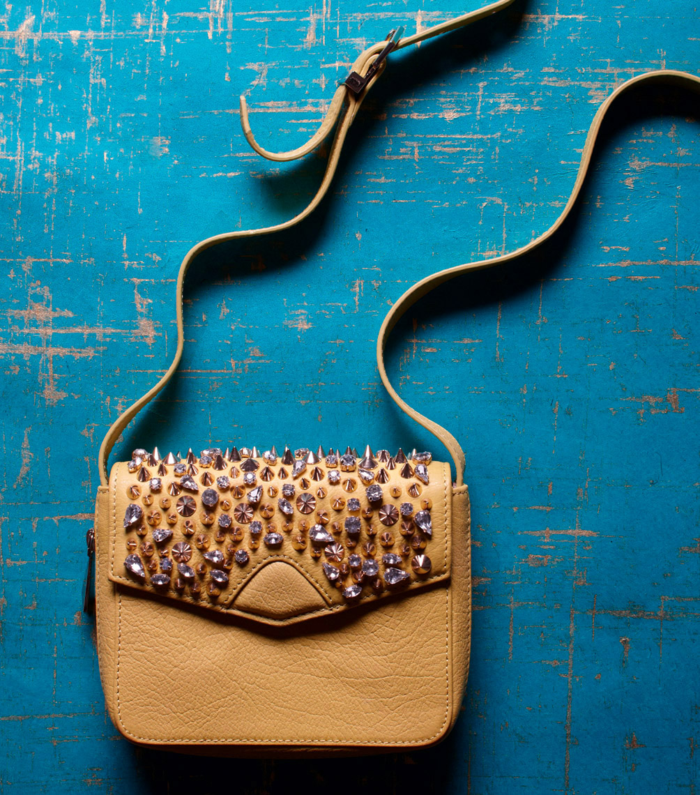 tan handbag with bejeweled top on blue wooden surface