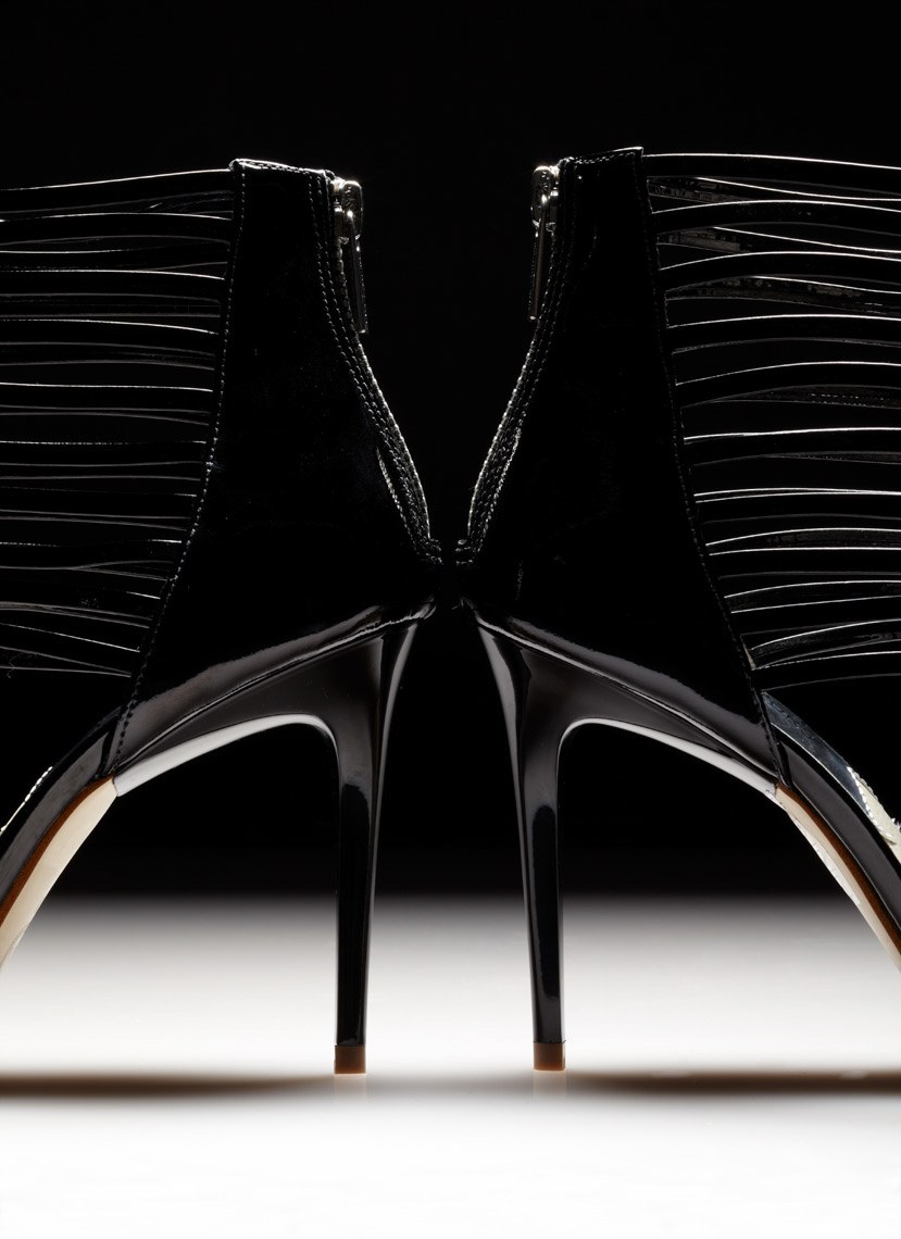 shiny black strappy stilettos with shadow on white surface