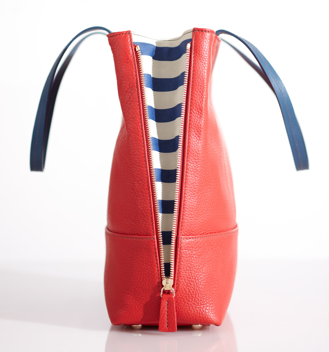 red zip-up handbag with blue handles and blue and white striped sides