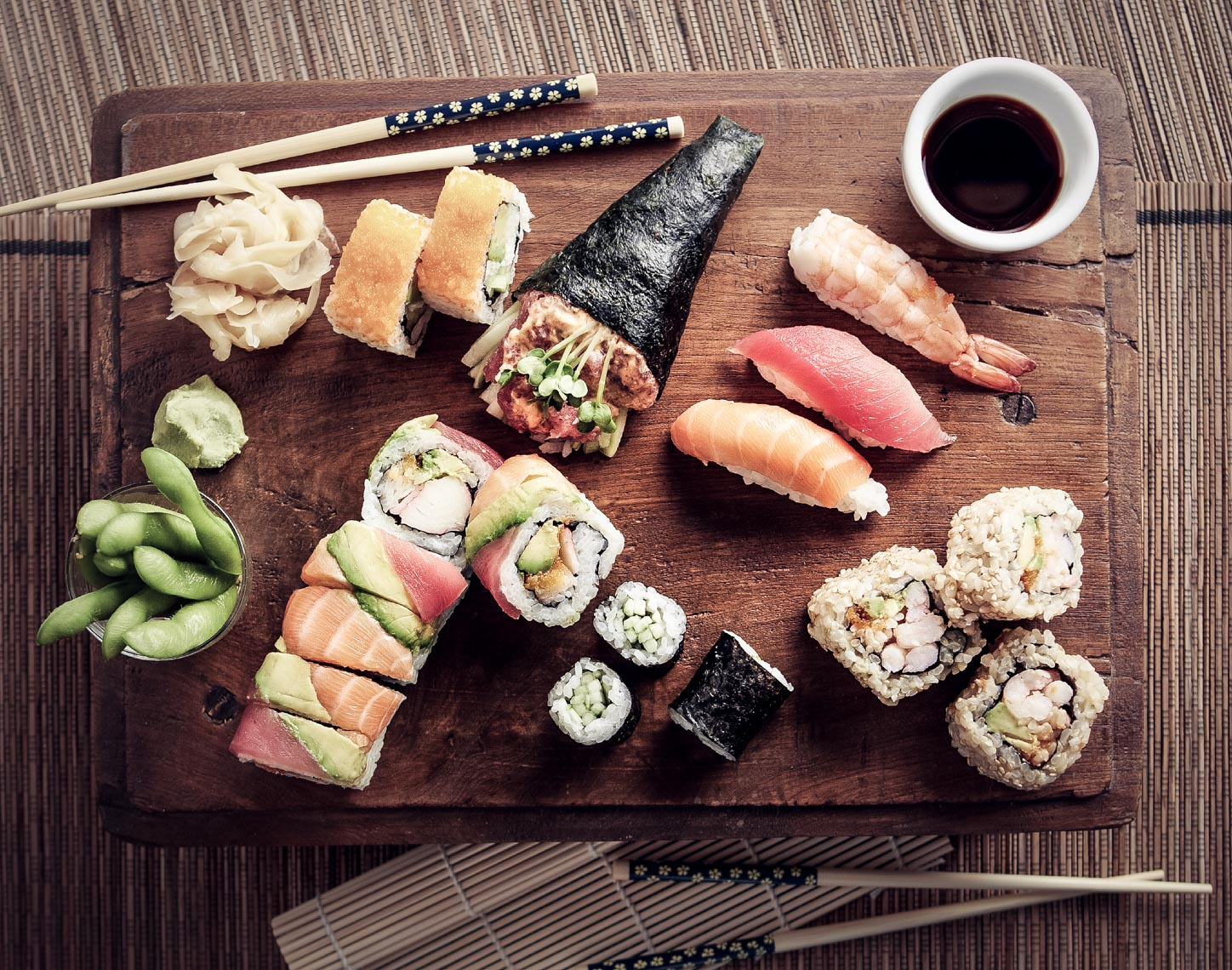 fresh sushi and sushi rolls with edamame and chopsticks on wooden surface
