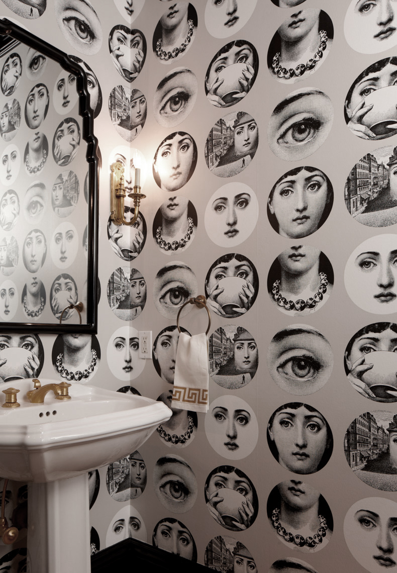 bathroom with black and white circular portrait wallpaper and white sink