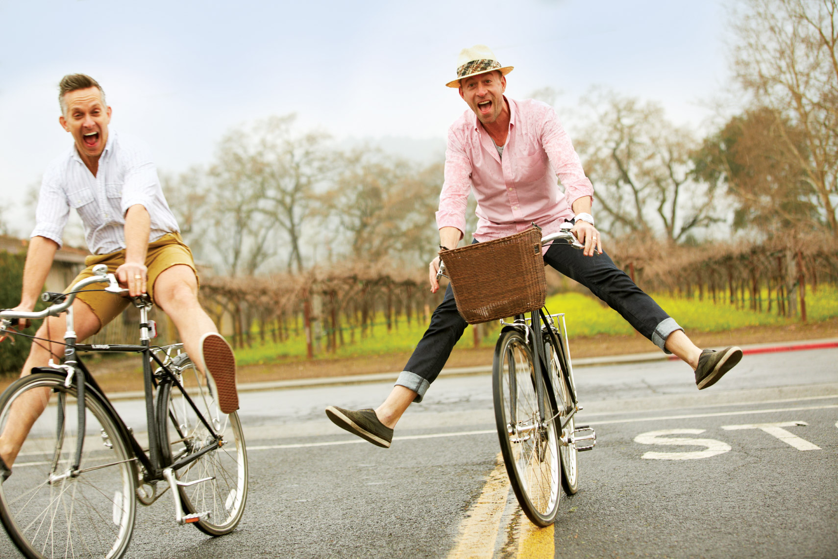 Two men ride  vintage bikes playfully with legs spread out on a street